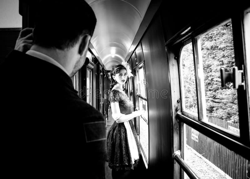 美丽的妇女在站立在有观看她的官员的走廊的机车的红色茶葡萄酒茶礼服穿戴了 免版税库存照片