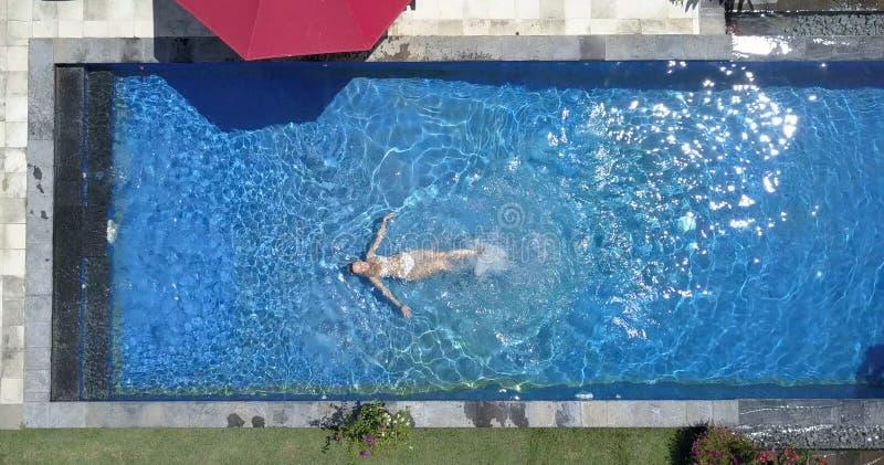 年轻美丽的妇女在水池,平展位置, dron视图游泳 免版税库存照片