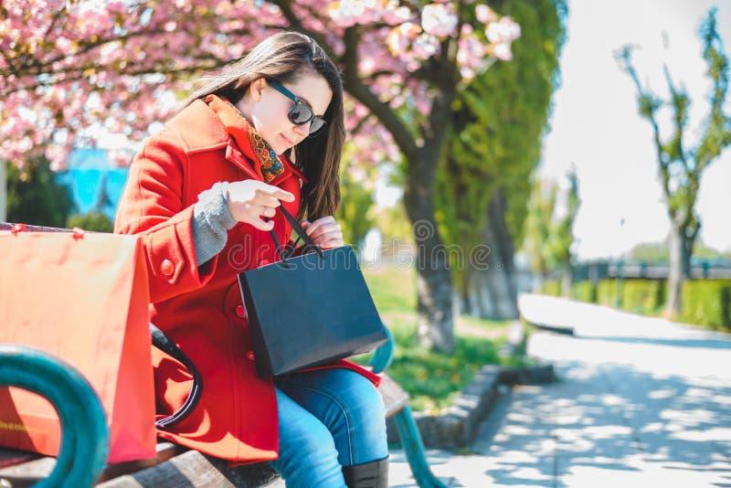 年轻美丽的妇女坐一条长凳在一个市中心与她的购物袋 免版税库存照片