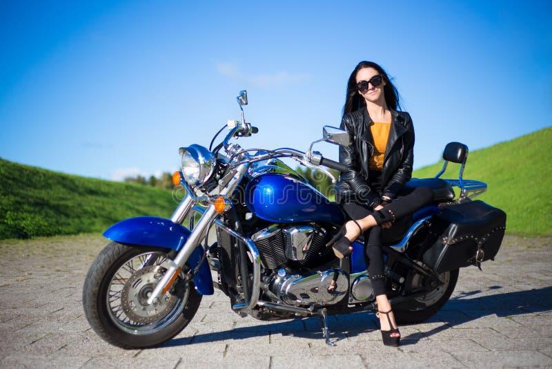年轻美丽的妇女坐减速火箭的摩托车 免版税库存照片