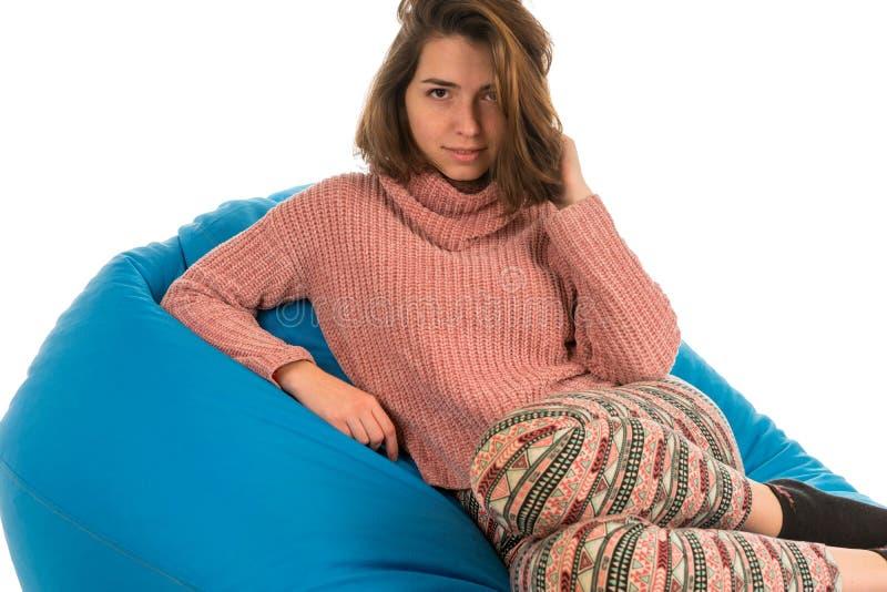 美丽的妇女坐客厅的蓝色装豆子小布袋沙发或 库存照片