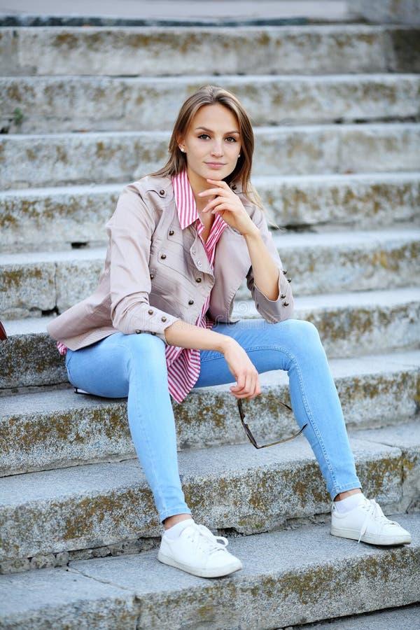 年轻美丽的妇女坐拿着太阳镜的石台阶 库存图片