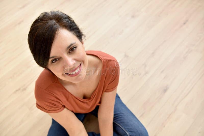 美丽的妇女坐木地板 免版税库存照片