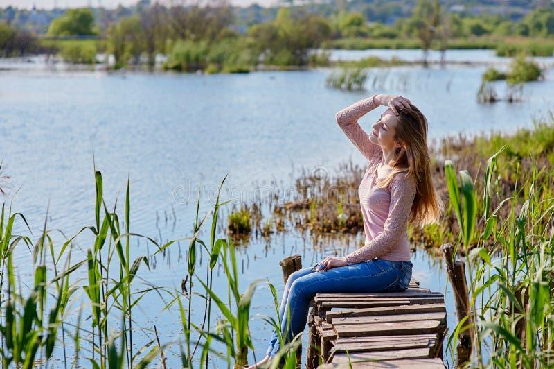 美丽的妇女坐木码头河 库存图片