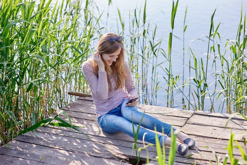 美丽的妇女坐木码头河 库存照片