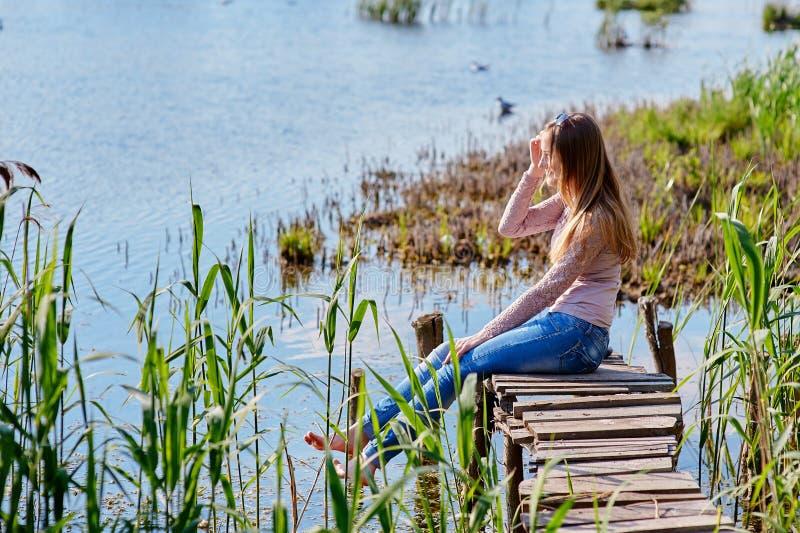 美丽的妇女坐木码头河 免版税库存图片