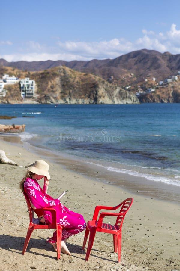 年轻美丽的妇女坐读一本书的海滩在Taganga 库存图片