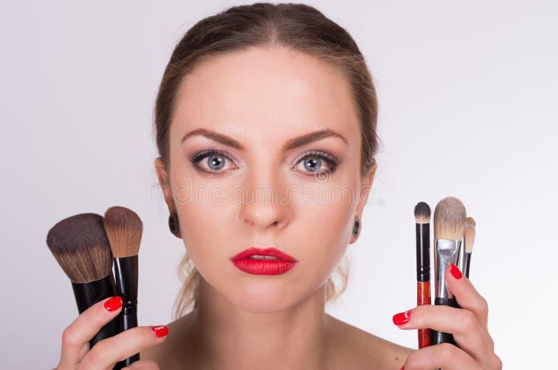 年轻美丽的妇女对负刷子临近她的面孔 免版税库存图片