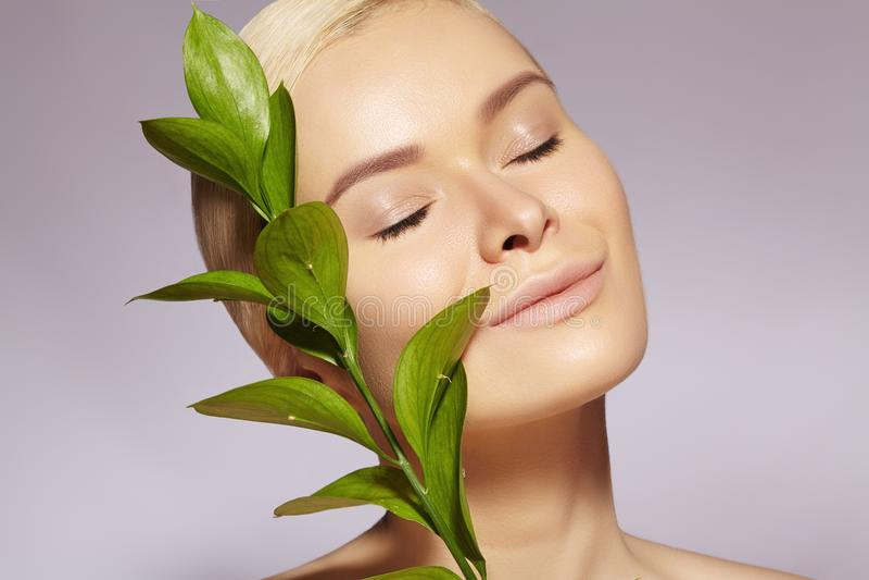 美丽的妇女应用有机化妆用品 温泉健康 与干净的皮肤的设计 医疗保健 与叶子的图片 库存图片