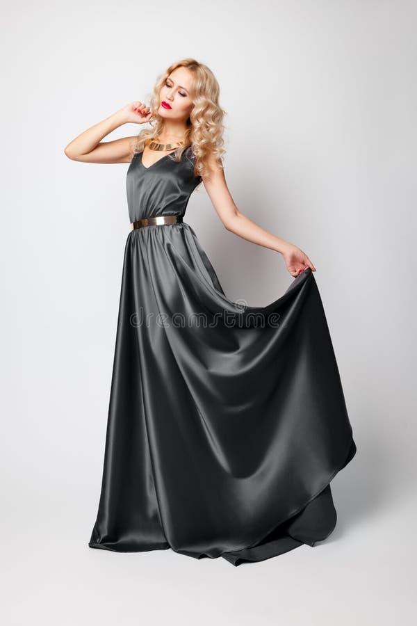 美丽的妇女式样摆在灰色礼服 免版税库存照片