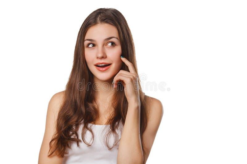 年轻美丽的妇女想法的注视着对边空白的拷贝空间,被隔绝在白色背景 免版税库存图片