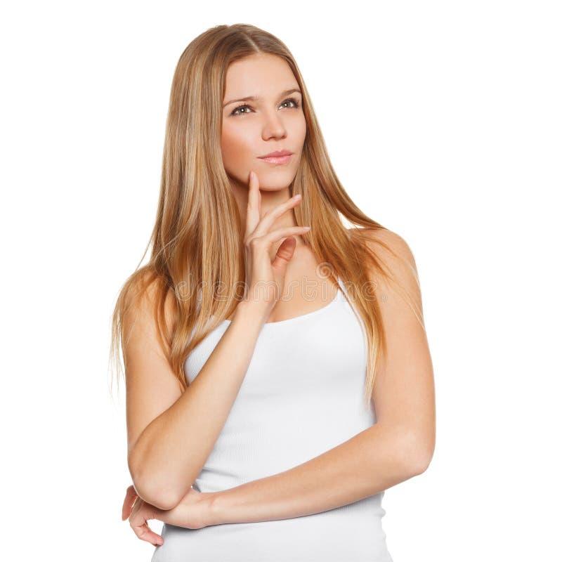 年轻美丽的妇女想法的注视着对边空白的拷贝空间 库存照片