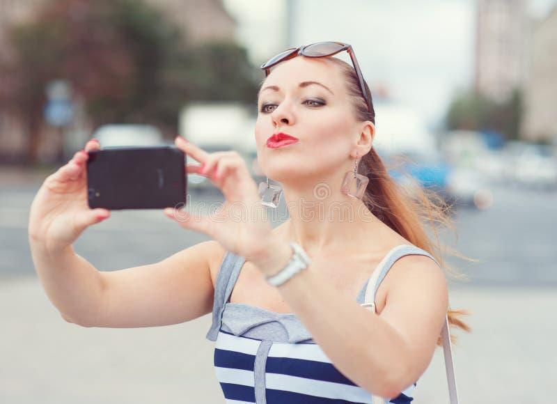 美丽的妇女拍的照片的她自己在城市 库存图片