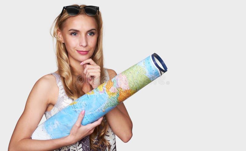 美丽的妇女拿着一张世界地图 免版税图库摄影
