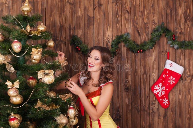 美丽的妇女挂上在圣诞树Christma的球 免版税图库摄影