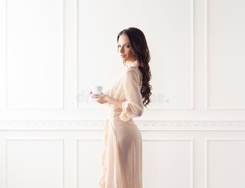 美丽的妇女时尚射击晨衣的 库存图片