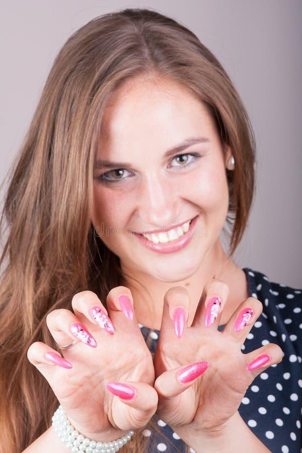 美丽的妇女显示她桃红色钉子 免版税库存图片