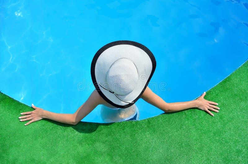 美丽的妇女晒日光浴由水池的,顶视图 免版税库存图片
