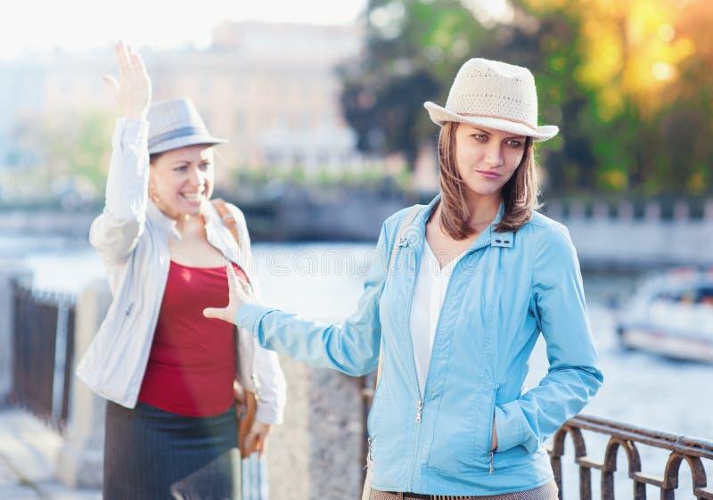 年轻美丽的妇女有与她的朋友的争吵在城市 图库摄影