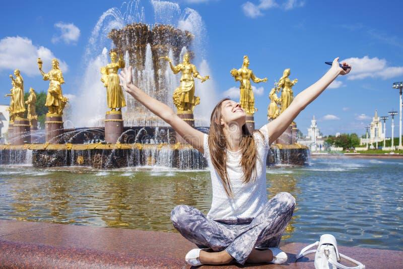 年轻美丽的妇女有坐在喷泉附近的休息 免版税图库摄影