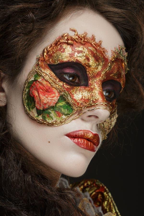美丽的妇女特写镜头画象葡萄酒礼服和面具的 免版税库存图片