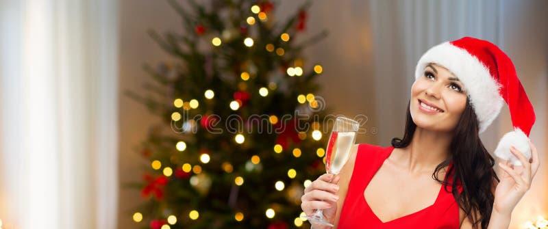 美丽的妇女用在圣诞树的香槟 免版税库存图片
