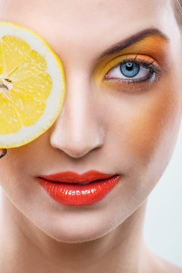 美丽的妇女用柠檬和黄色构成-接近  库存图片