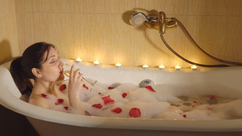 美丽的妇女由烛光洗浴并且喝香槟 免版税库存照片