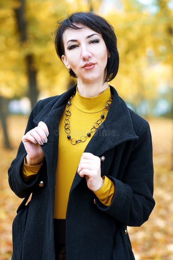 美丽的妇女画象室外的秋天,黄色叶子和树在背景,秋季 免版税库存图片