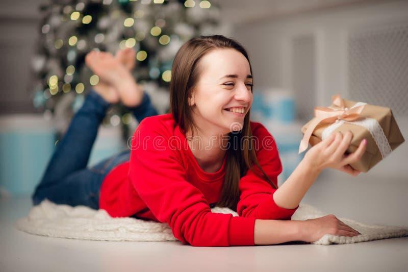 美丽的妇女画象有在家坐由圣诞树的礼物的 免版税库存照片