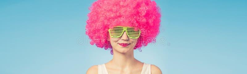 美丽的妇女画象桃红色假发和绿色玻璃的 免版税库存照片