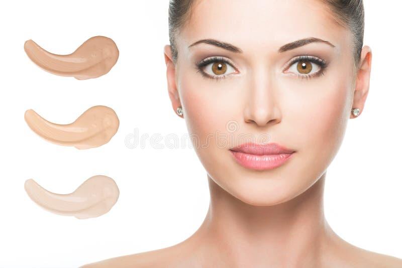 美丽的妇女的式样面孔有基础的在皮肤 库存照片