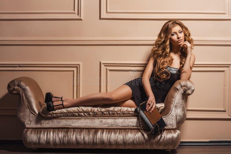 年轻美丽的妇女的迷人的画象皮鞋和时髦的提包的 免版税库存照片