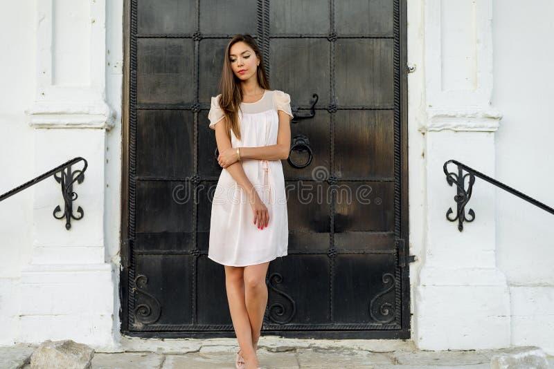 美丽的妇女站立在城堡的黑门的,哥特式教会 一件桃红色礼服的女孩,摆在紧密,休息 图库摄影