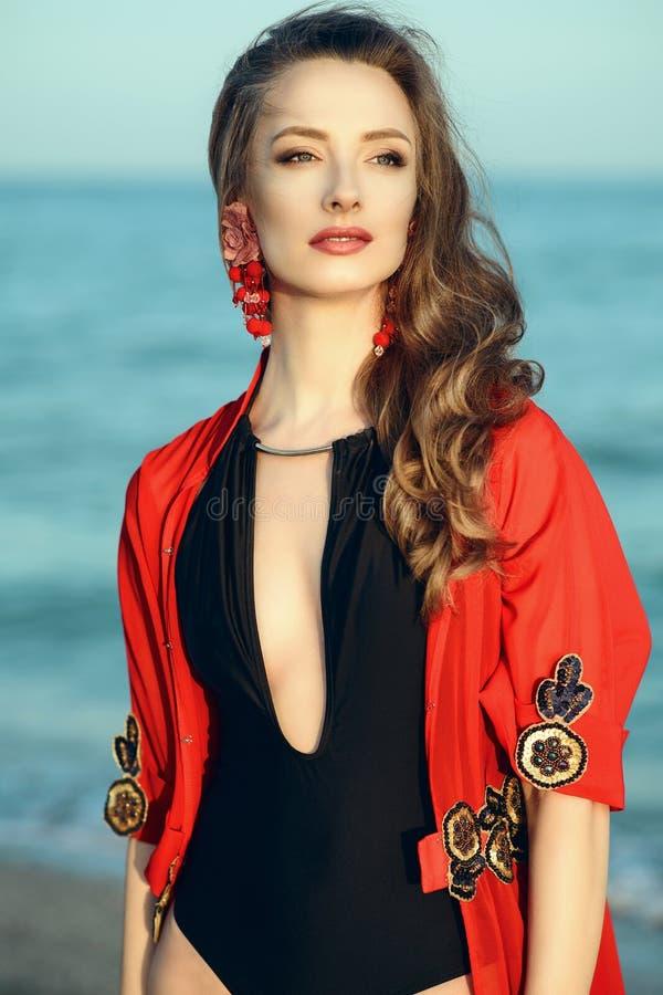 美丽的妇女站立在海边的穿时髦一件三角背心脖子泳装和红色东方海滩掩盖 免版税库存照片