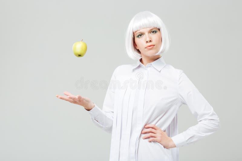 美丽的妇女站立的和投掷的苹果在天空中 免版税图库摄影