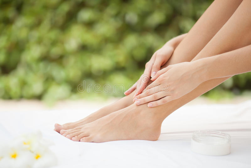 美丽的妇女腿和奶油。 免版税库存照片