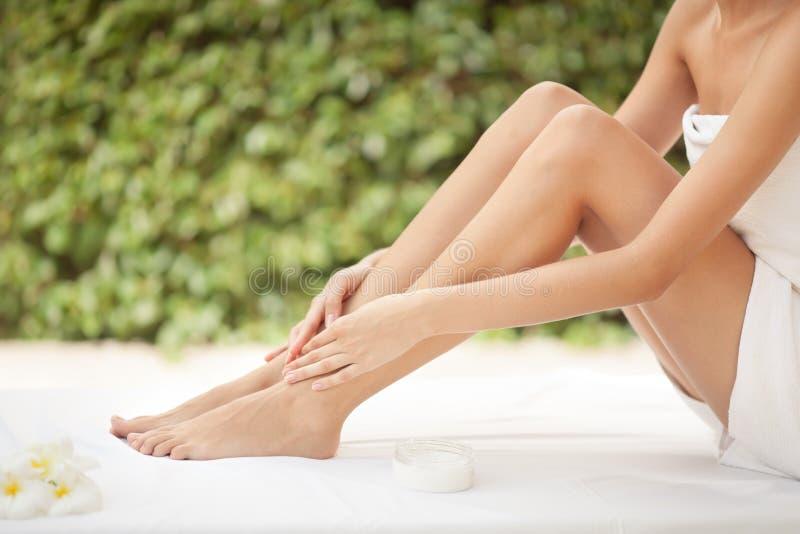 美丽的妇女腿和奶油。 免版税库存图片
