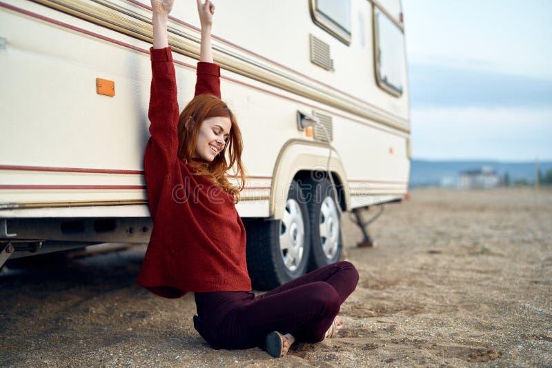 年轻美丽的妇女舒展在海滩的在拖车,旅行,夏天 免版税库存图片
