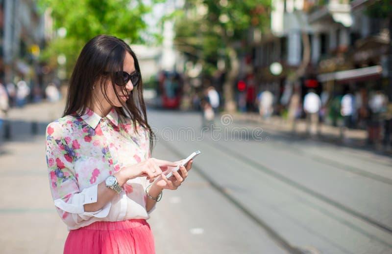 年轻美丽的妇女谈话在她的电话 库存图片
