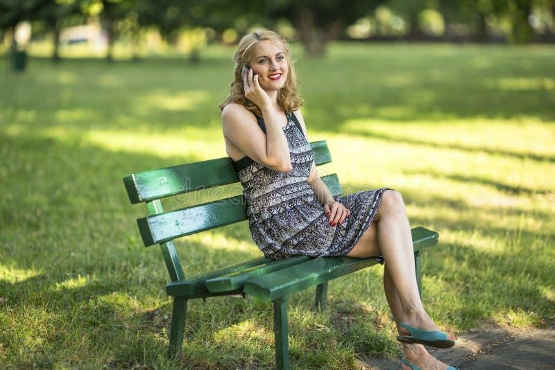 美丽的妇女谈话在手机坐长凳户外 库存照片