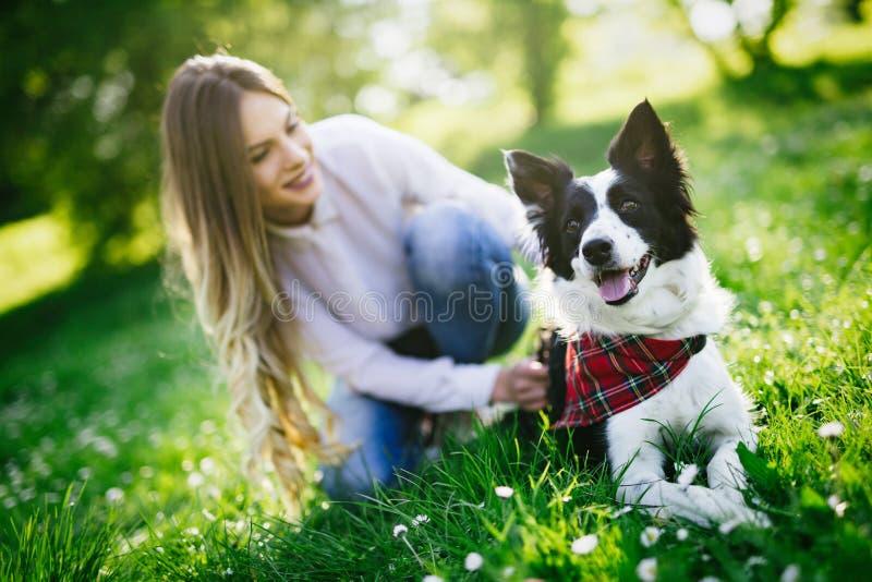 美丽的妇女走的逗人喜爱的狗本质上 免版税图库摄影