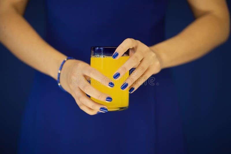 美丽的妇女递拿着杯在她的蓝色礼服前面的明亮的橙黄柠檬水 免版税图库摄影