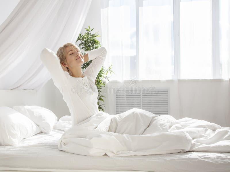 美丽的妇女醒了和坐一张白色床 免版税库存图片