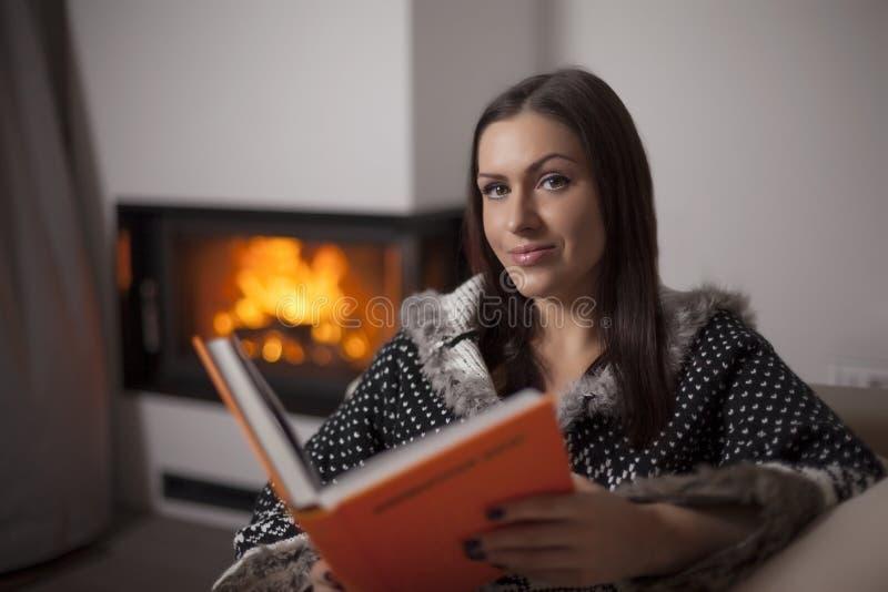 美丽的妇女阅读书画象由壁炉的 免版税库存图片