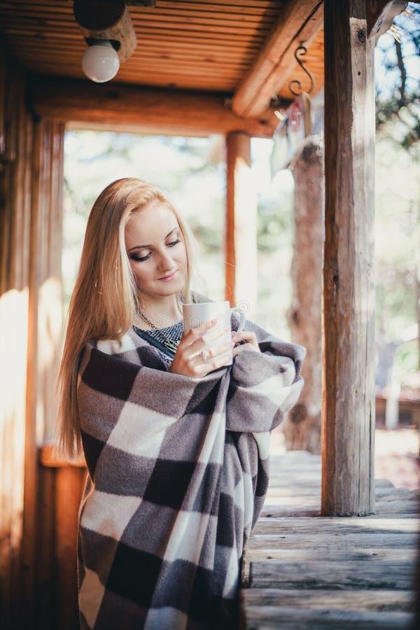 年轻美丽的妇女饮用的可可粉在一个木coutry房子里 库存照片