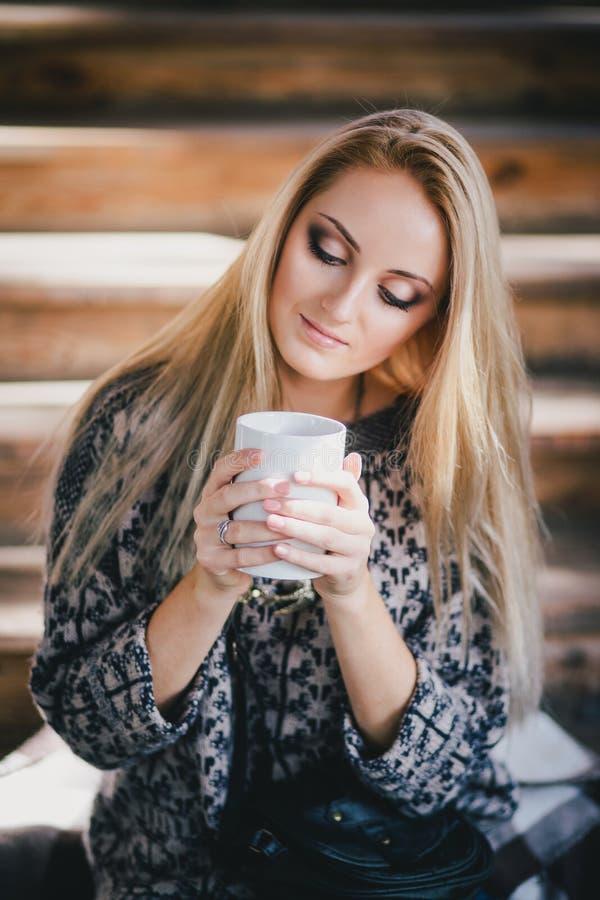 年轻美丽的妇女饮用的可可粉在一个木coutry房子里 图库摄影