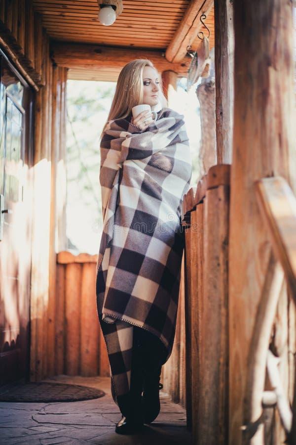年轻美丽的妇女饮用的可可粉在一个木coutry房子里 库存图片
