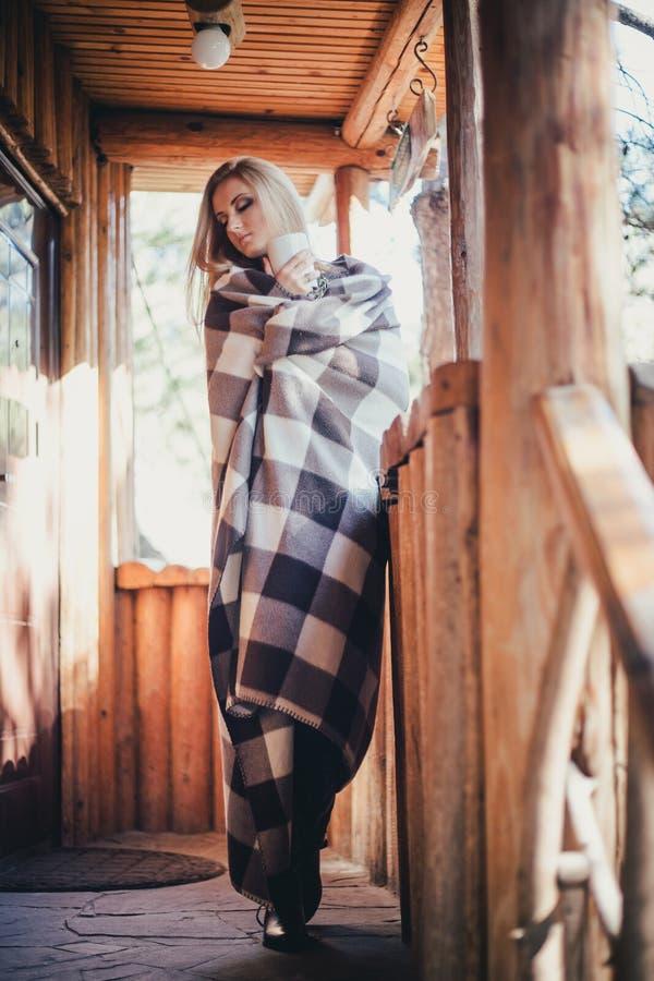 年轻美丽的妇女饮用的可可粉在一个木coutry房子里 免版税图库摄影