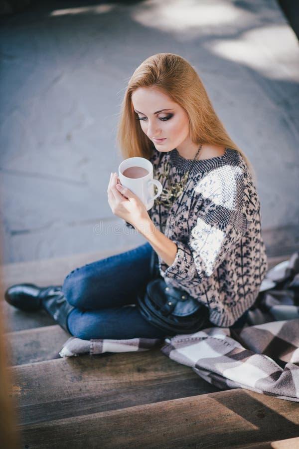 年轻美丽的妇女饮用的可可粉在一个木coutry房子里 免版税库存照片